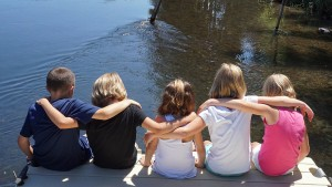children sitting on the end of the dock with their feet in the water