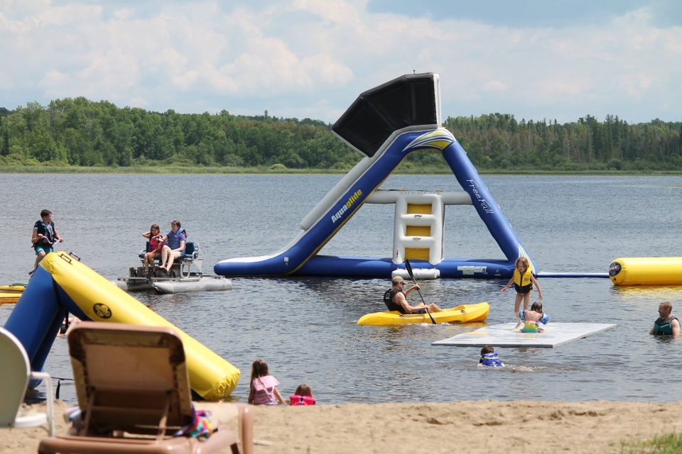 adults and kids having fun on the water toys at our beach